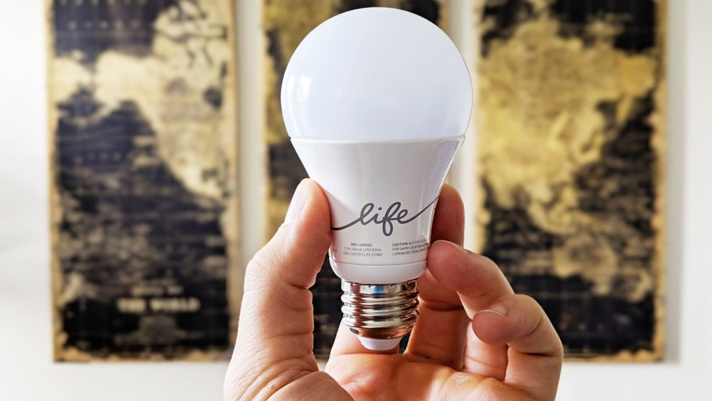 Hand holding a C-Life by GE smart bulb